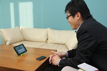 タブレットを通じて、取材に参加してくださった仙台のメンバーと打ち合せをする大達氏